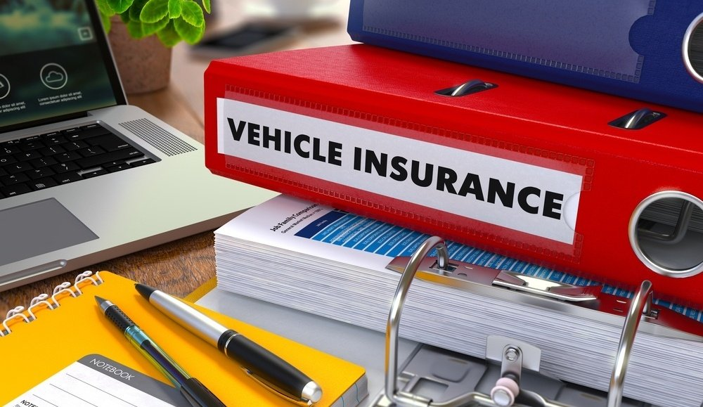 Red Ring Binder with Inscription Vehicle Insurance on Background of Working Table with Office Supplies, Laptop, Reports. Toned Illustration. Business Concept on Blurred Background.-697592-edited.jpeg
